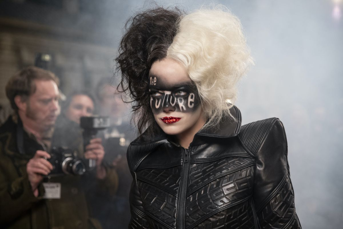 Emma Stone as Cruella de Vil. She has black and white hair and is dressed in a structured leather ballgown.