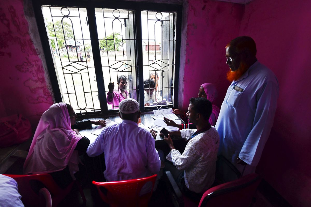 Four people sit at a table in front of an ornate window in India.