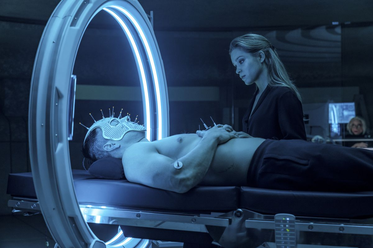 Okay, you got me on this one. Uh, a shirtless Mark Wahlberg is lying on his back on what looks like a hospital bed, wearing a mesh face mask covered with spikes topped with LEDs? And his head is through some kind of big ring lined with blue florescent lights? And Sophie Cookson is looking on a little judgmentally? Anyway, this happens in Infinite.