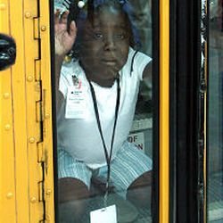 Jamie Se'Maj Lollis, a 6-year-old evacuee, cries and bangs on the door of a school bus taking her to an elementary school in Houston.