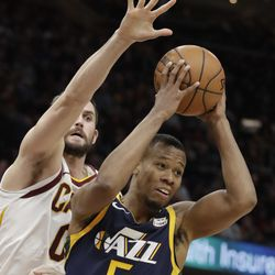 Utah Jazz's Rodney Hood (5) looks to pass against Cleveland Cavaliers' Kevin Love (0) in the first half of an NBA basketball game, Saturday, Dec. 16, 2017, in Cleveland. (AP Photo/Tony Dejak)