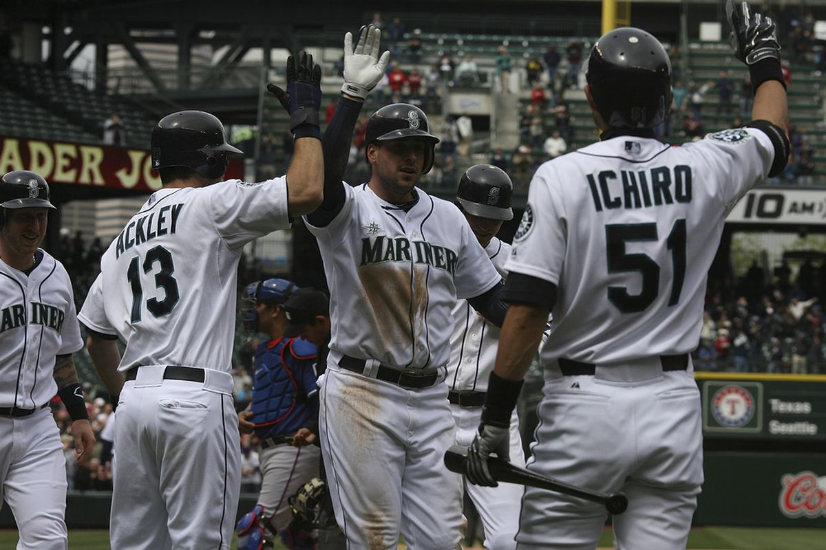 SEATTLE, WA - MAY 23:  Alex Liddi #16 of the Seattle Mariners is congratulated by teammates after hitting a grand slam against the Texas Rangers at Safeco Field on May 23, 2012 in Seattle, Washington. (Photo by Otto Greule Jr/Getty Images)