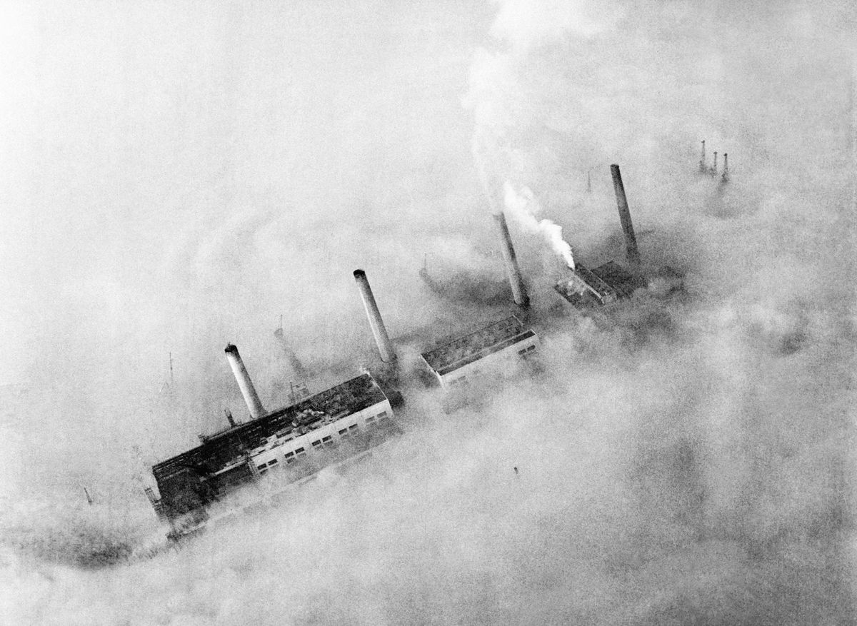 The chimneys of a London factory rise out of the smog, 1952