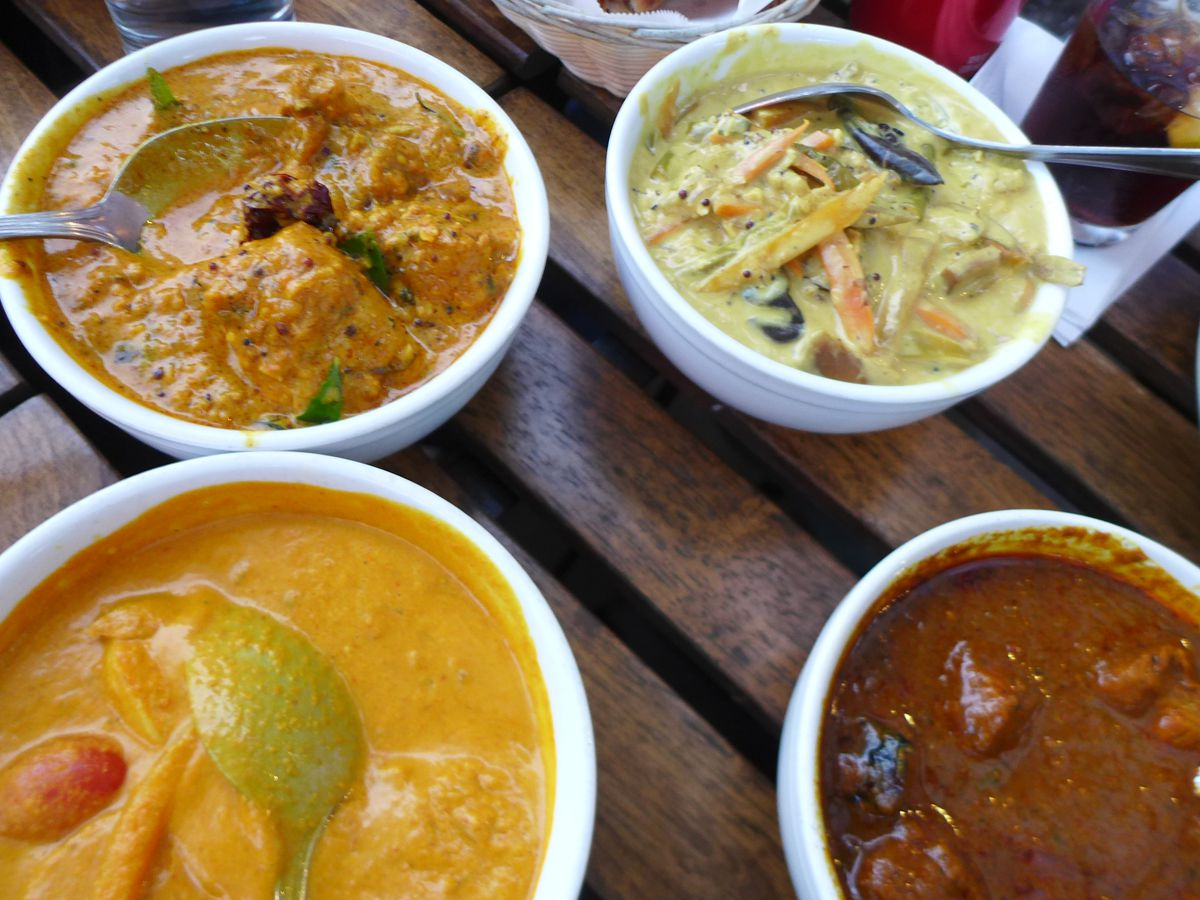Four bowls of curry in shades of brown, dark red, and orange on a slatted table.