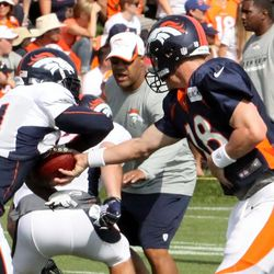 Peyton Manning slides the ball into running back Ronnie Hillman's hands during practice.