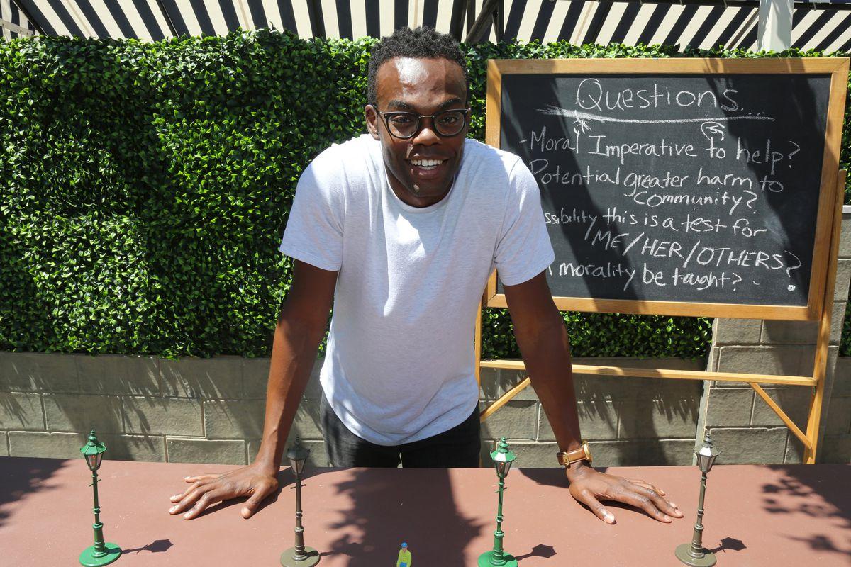 """The character Chidi Anagonye on the TV show """"The Good Place"""" stands in front of a chalkboard covered in questions."""