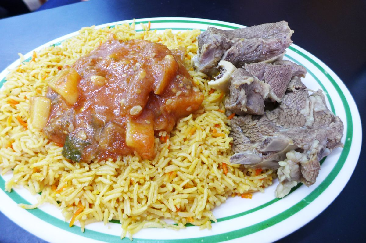 A plate contains yellow rice, a vegetable curry with a pink tinge, and boiled lamb with bones.