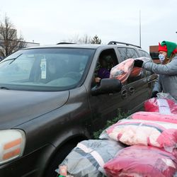 Jill Sandstrom hands a coat to a recipient during the Big Brothers Big Sisters Holiday Drive Thru at a parking lot in Taylorsville on Thursday, Dec. 10, 2020.During the event, Littles (youths living in adversity), their Bigs (volunteer mentors) and their families were invited to pick up warm winter coats, gift cards and fun treats.