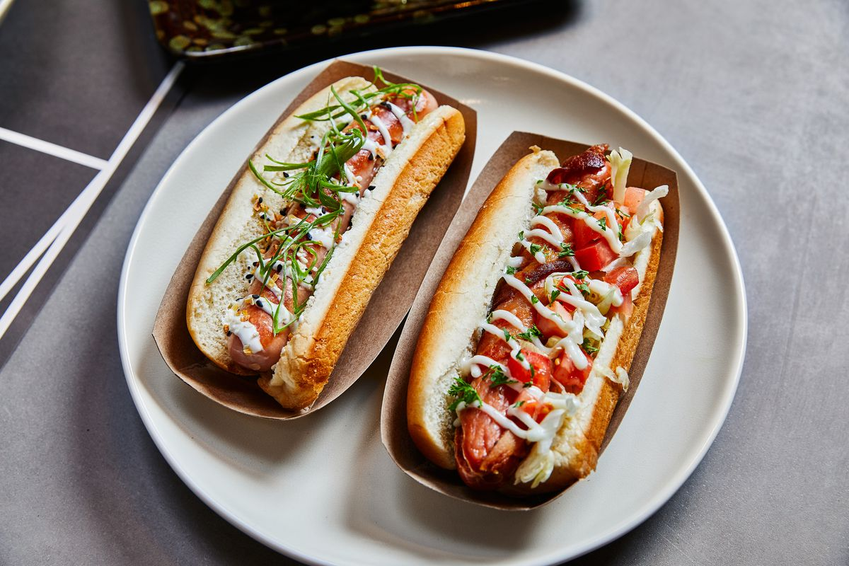 Two hot dogs sitting in cardboard holders on a white plate