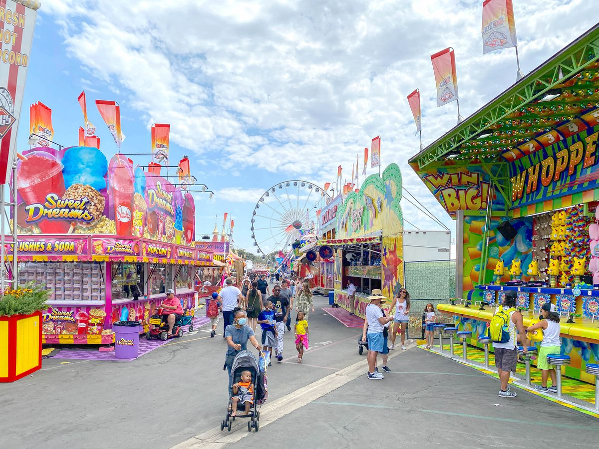 A shot down the middle of a midway at a state fair with games and food on all sides.