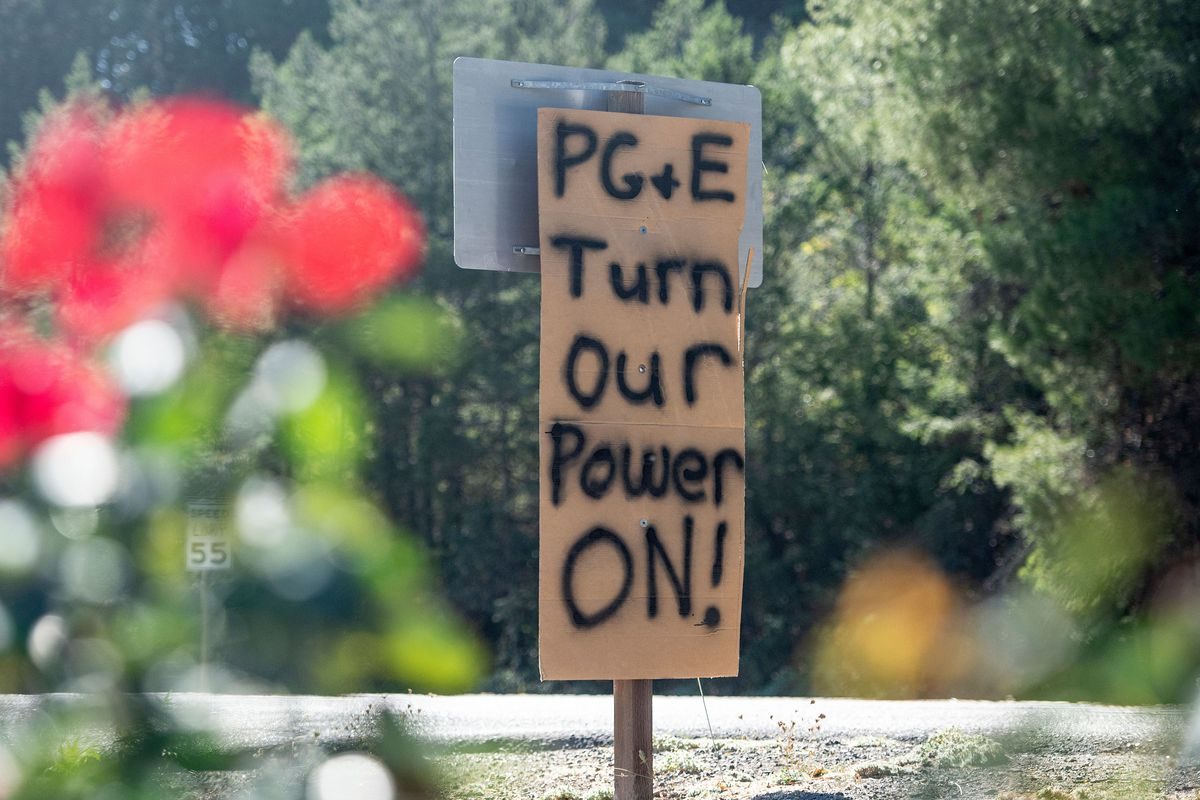 """A hand-lettered cardboard sign reading, """"PG&E, turn our power on."""""""