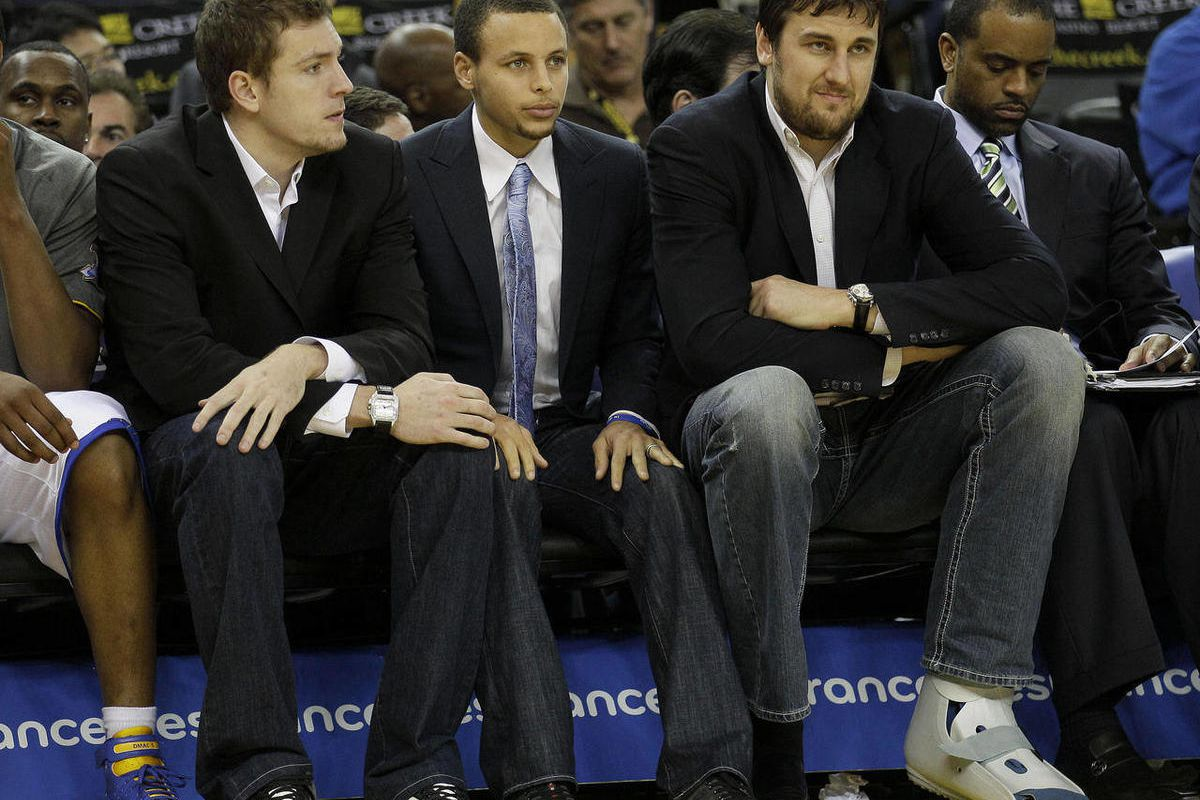 Injured Golden State Warriors players David Lee, from left, Stephen Curry, and Andrew Bogut, from Australia, sit on the bench during the third quarter of an NBA basketball game against the San Antonio Spurs in Oakland, Calif., Monday, April 16, 2012.
