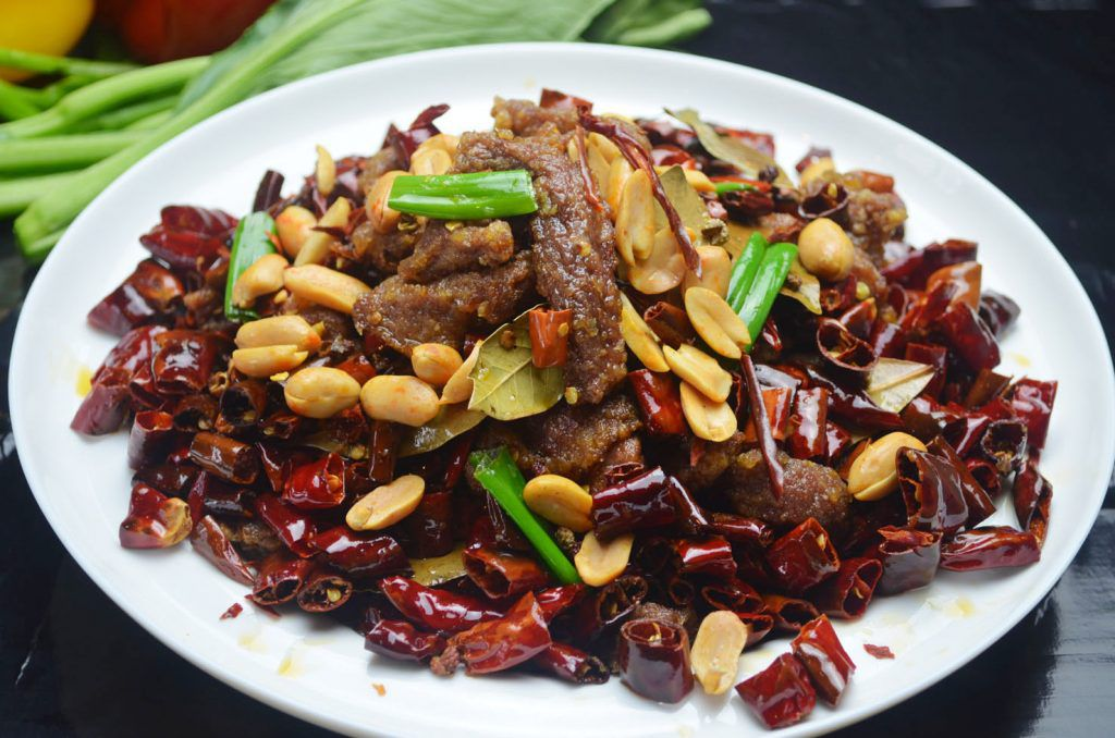 A bowl of beef with chili peppers.