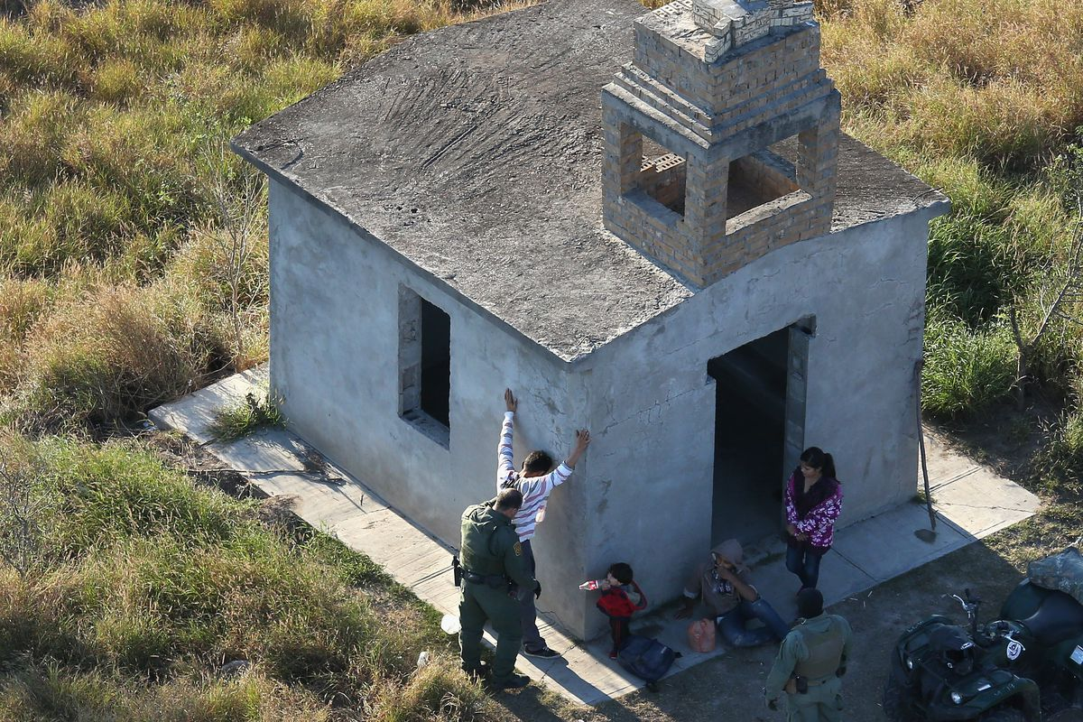 A Border Patrol agent searches a Central American man crossing into the US.