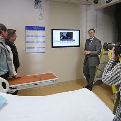 Cory Smith, project manager for Intermountain Healthcare's transformation lab, shows senior French health officials a hospital room of the future that includes new monitoring devices and a touchscreen for viewing and inputing patient information during a tour of IHC in Murray on Wednesday, Jan. 27, 2016.  The French officials were in Utah to learn about how care is delivered here.