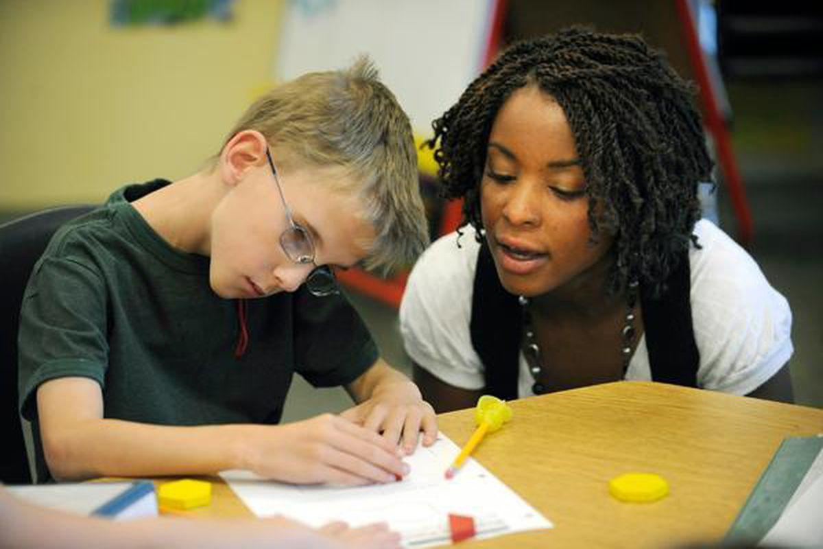 A teacher helps a student who has cerebral palsy.