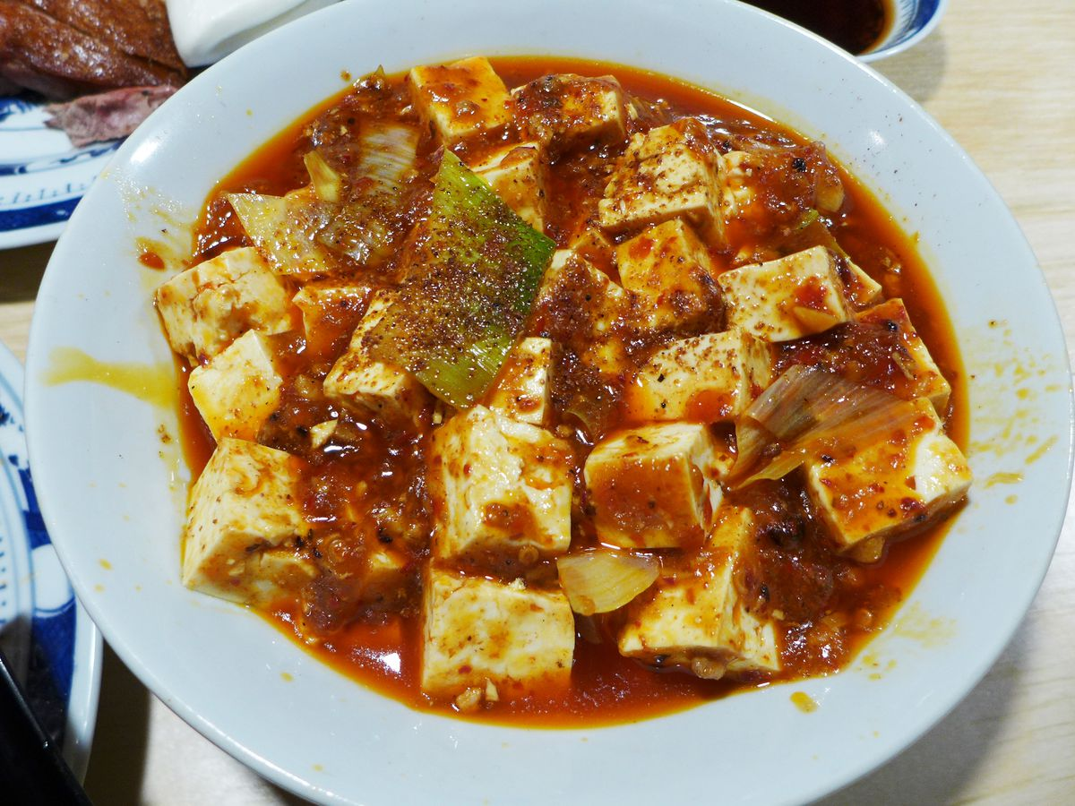 A bowl of jiggly tofu engulfed in brown sauce.