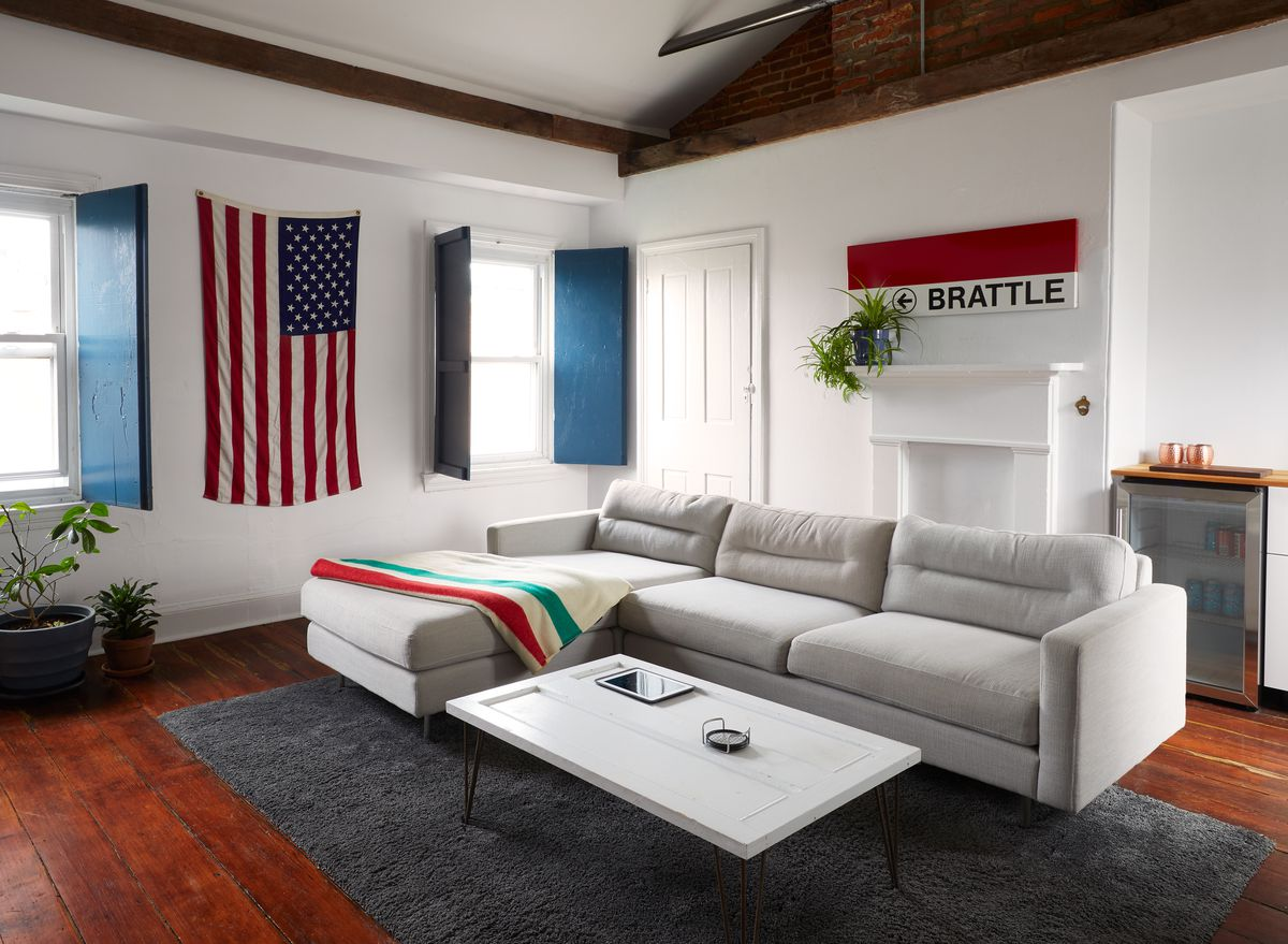 A living area. There is a large white couch, white walls, a fireplace, and two windows with blue window openings. The floor is hardwood and there is a coffee table.