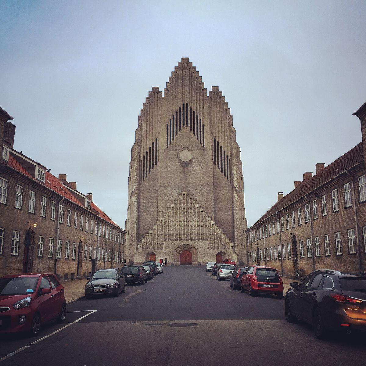 """The exterior of <span data-author=""""843"""">Grundtvig's Church in Denmark, The facade resembles a church organ and is comprised of tan brick. There are attached houses leading up to the church on a street in the foreground.</span>"""