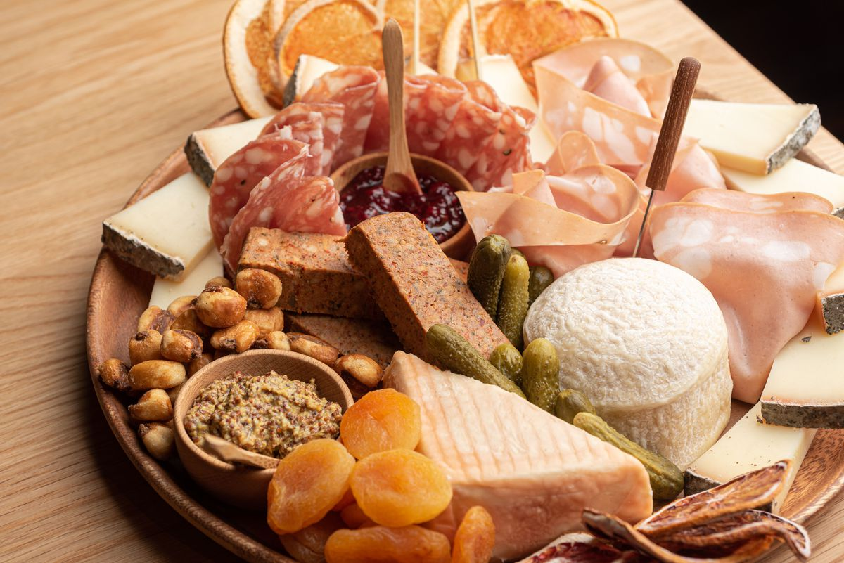 A round wooden board of meat and cheese with a collection of jams and spreads as well.