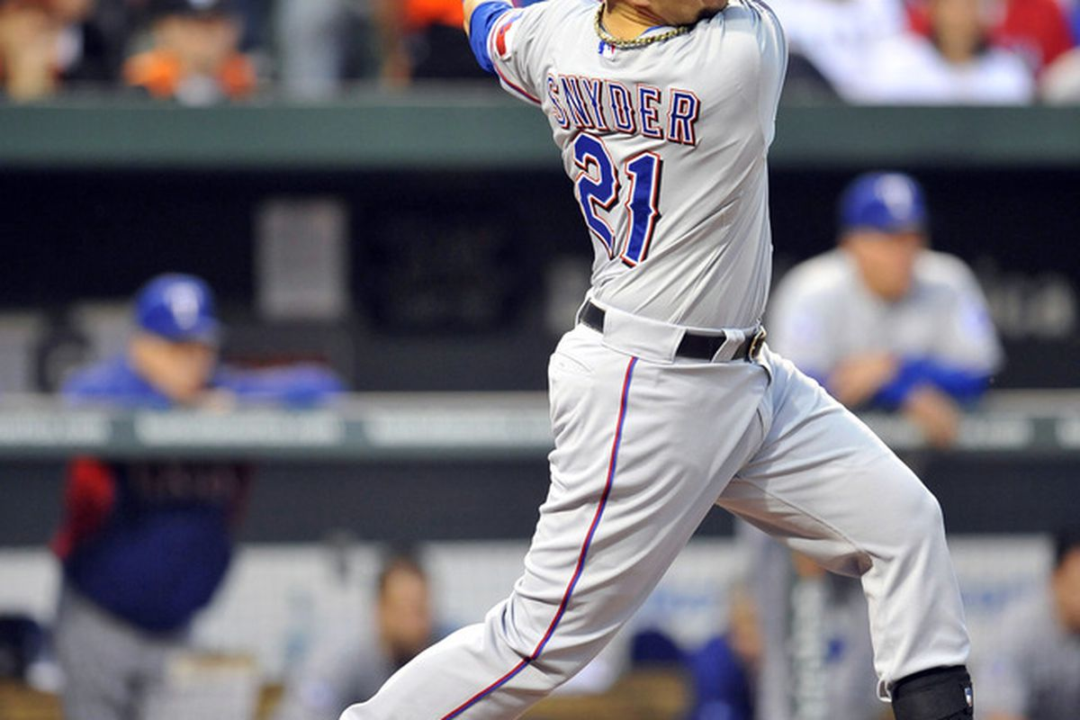 May 7, 2012; Baltimore, MD, USA; Texas Rangers third baseman Brandon Snyder (21) hits a two-run RBI single in the second inning against the Baltimore Orioles at Oriole Park at Camden Yards. Mandatory Credit: Joy R. Absalon-US PRESSWIRE