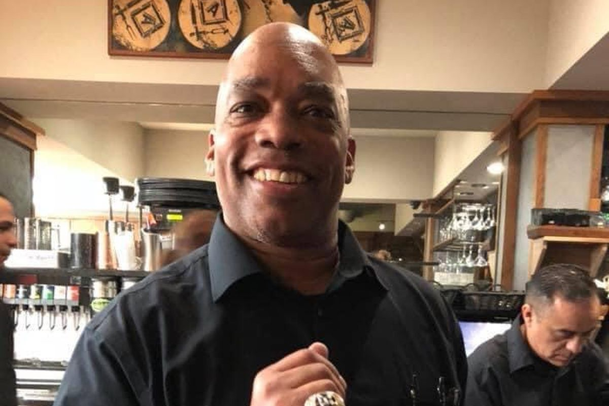 A Black man wearing a black button-down shirt stands in a kitchen with a big smile on his face