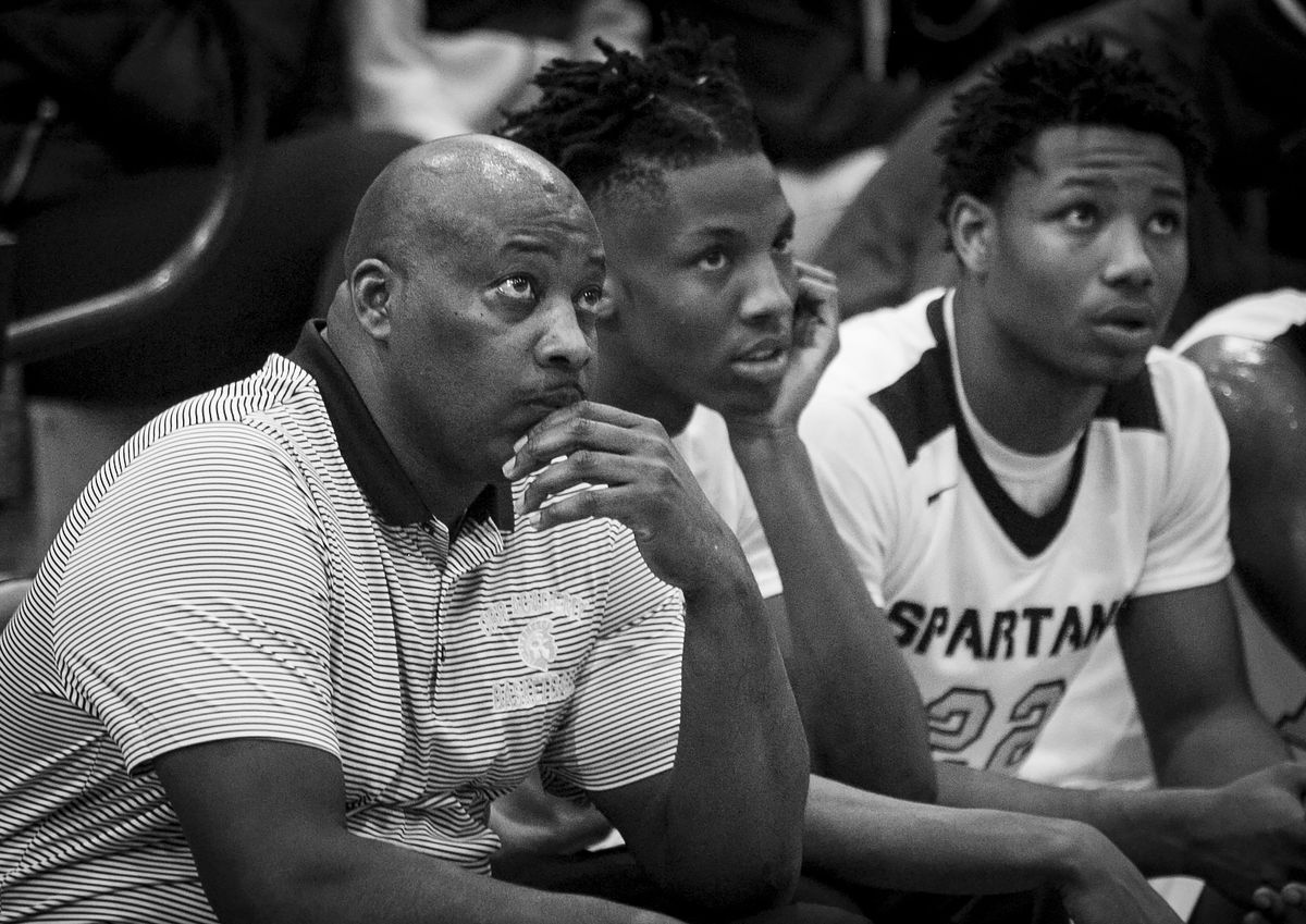 Coach Lou Adams, seated next to Tyron Mosley, watches from the bench as his team beats Westinghouse College Prep 58 – 55 at Orr Academy High School, Jan. 11, 2017.