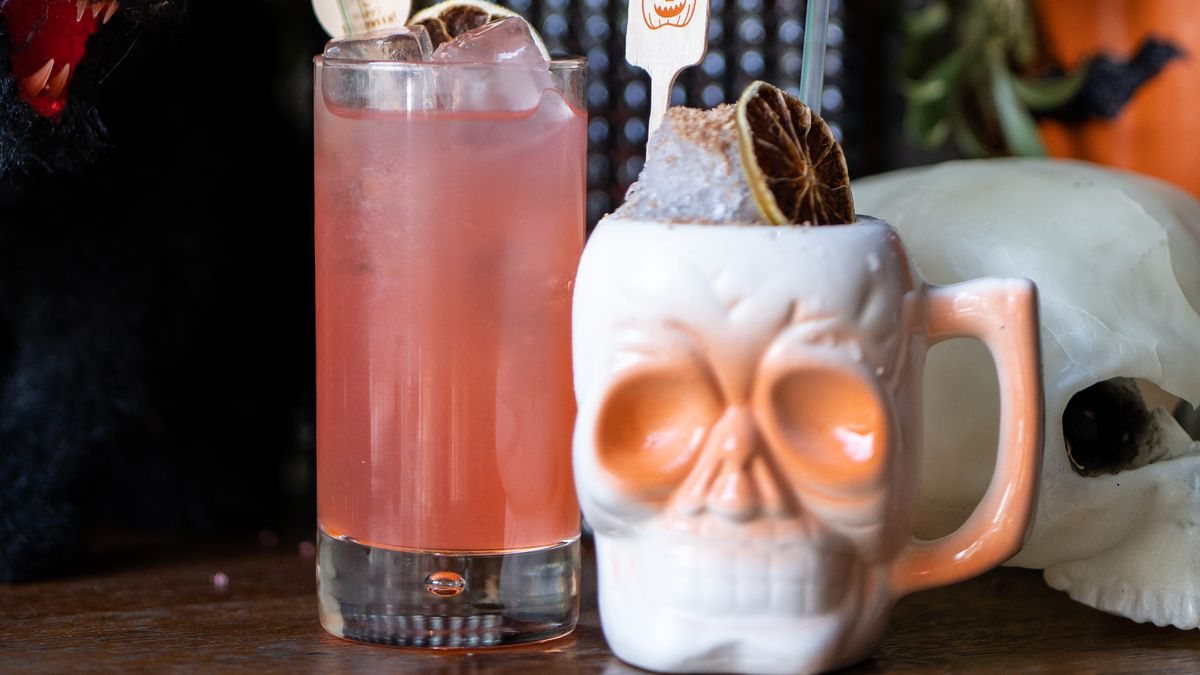 Two cocktails, one in a skull-shaped mug, and another in a tall glass with a straw sit in front of a background of Halloween decor.