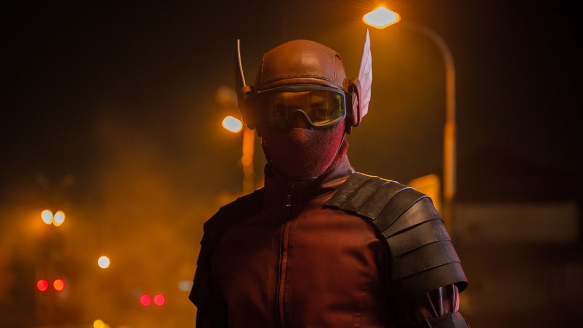 a man in a red mask with wings stands on a hazy street lit by orange street lights