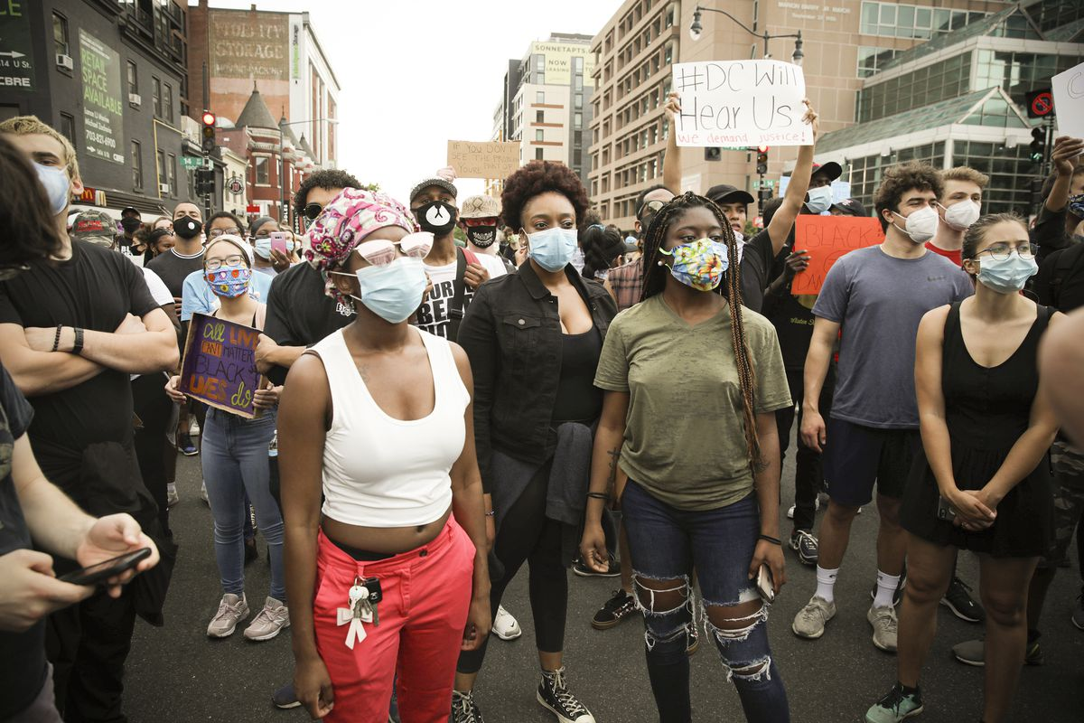 "A group of black women in blue face masks stand together in the center of the photo. Around them are clusters of protesters, one of whom is holding a large sign reading, ""#DC will hear us."""