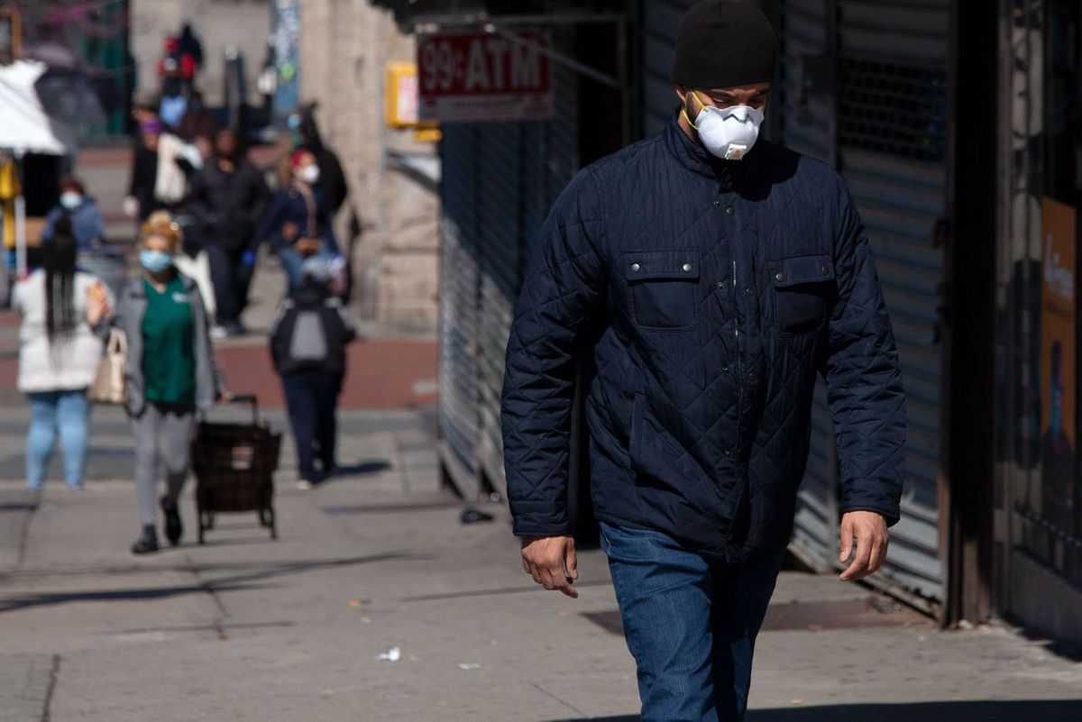 People shop and walk along East 161st Street in the South Bronx during the coronavirus outbreak.