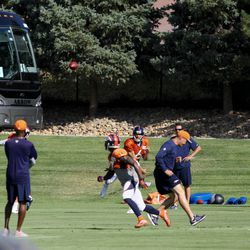 Broncos QB Mark Sanchez throws a pass to rookie WR Mose Fraizer during warmups at training camp.