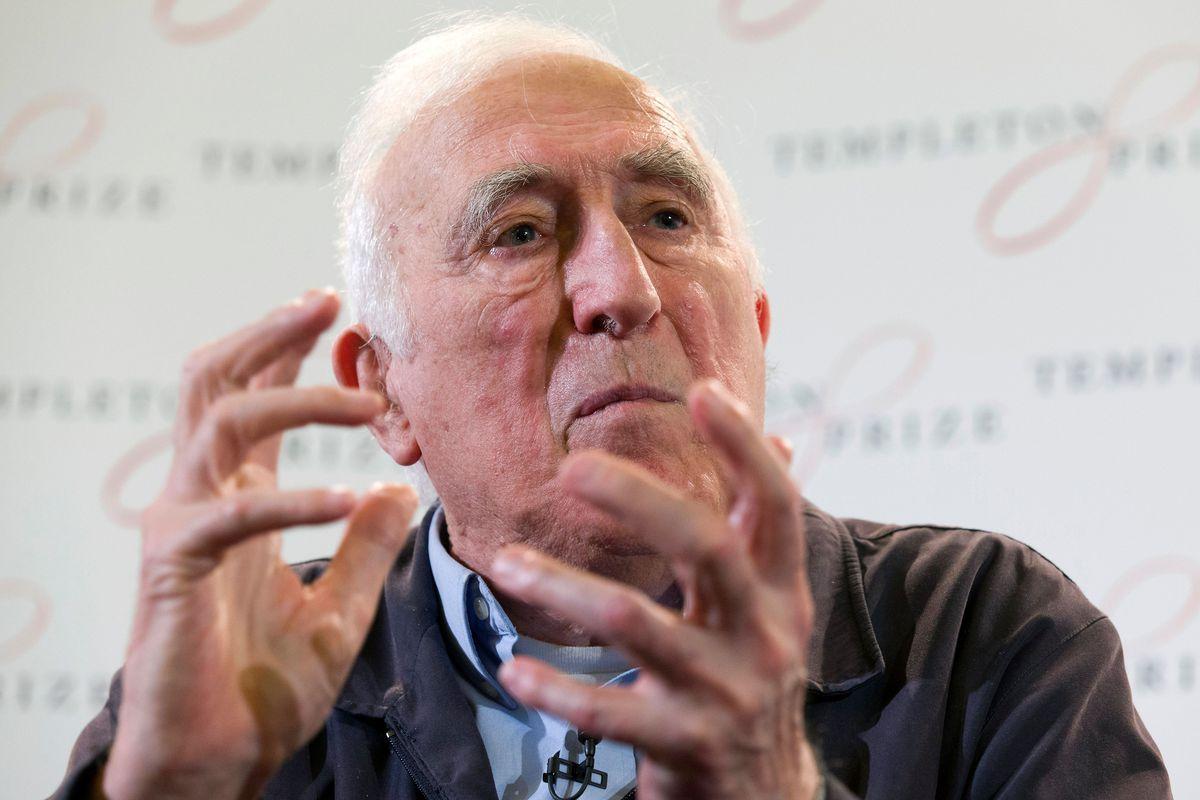 Vanier, in a dark jacket, gestures while looking stern.
