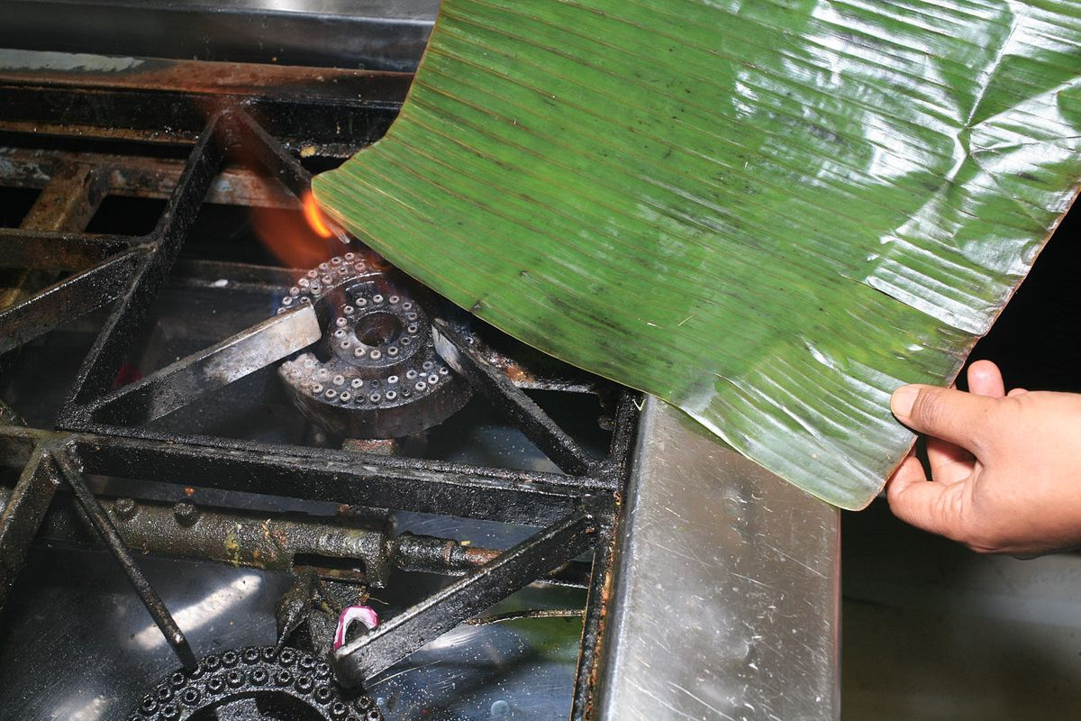 A banana leaf is charred over an open gas hob, catching its corner alight with an orange flame
