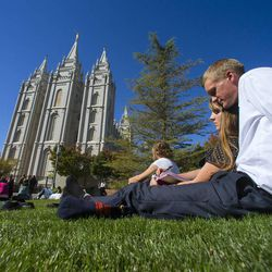 Sam Davidson and Ailina Smith listen to the talks while sitting on the church plaza near the Salt Lake Temple during the morning session of the 183rd Semiannual General Conference for the Church of Jesus Christ of Latter-day Saints Sunday, Oct. 6, 2013.