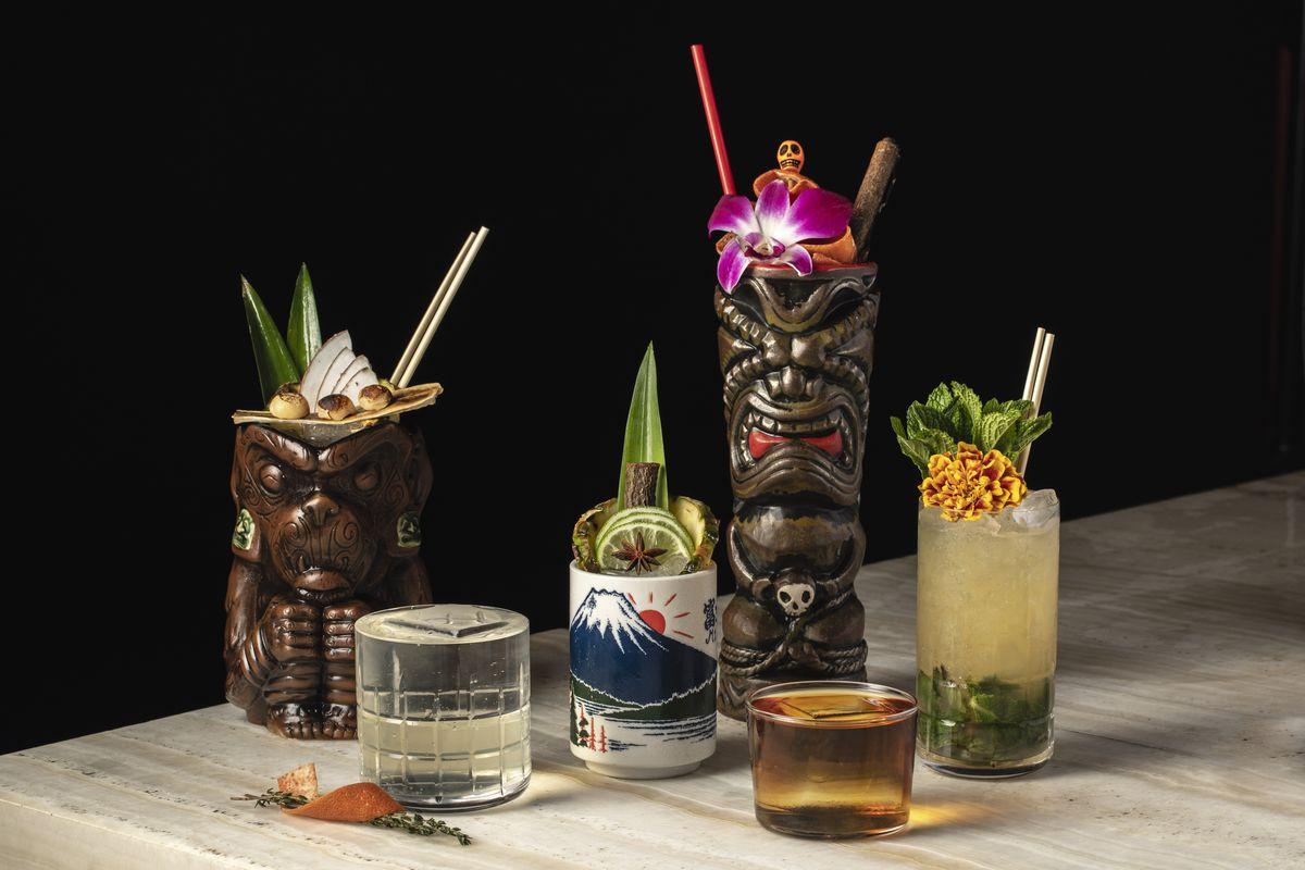 Six tiki cocktails in elaborate glasses.