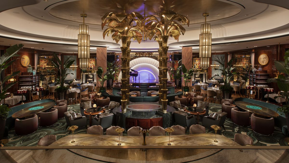 A stunning dining room in greens and golds with four gold palm trees and a stage with a grand piano in the background