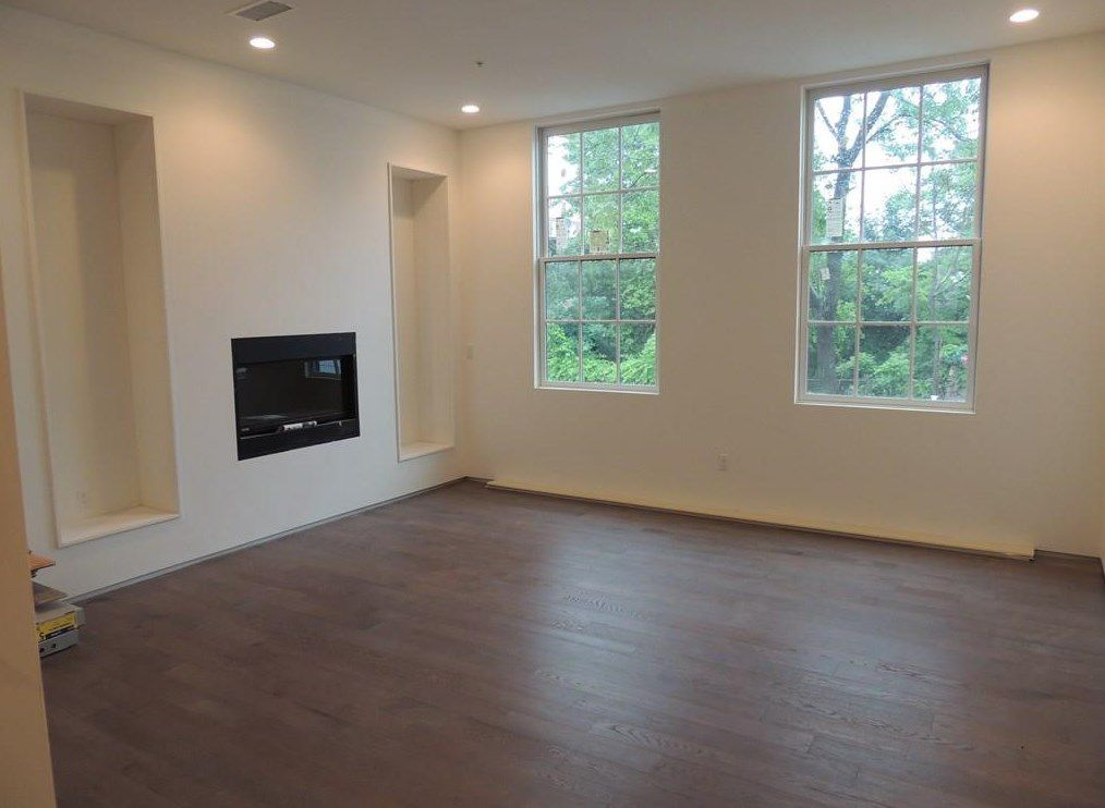 An empty living room with two empty alcove shelves, two windows, and a built-in fireplace.