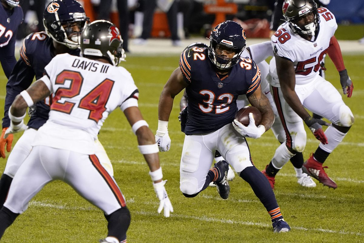 Chicago Bears running back David Montgomery (32) rushes the ball against Tampa Bay Buccaneers cornerback Carlton Davis (24) during the fourth quarter at Soldier Field.