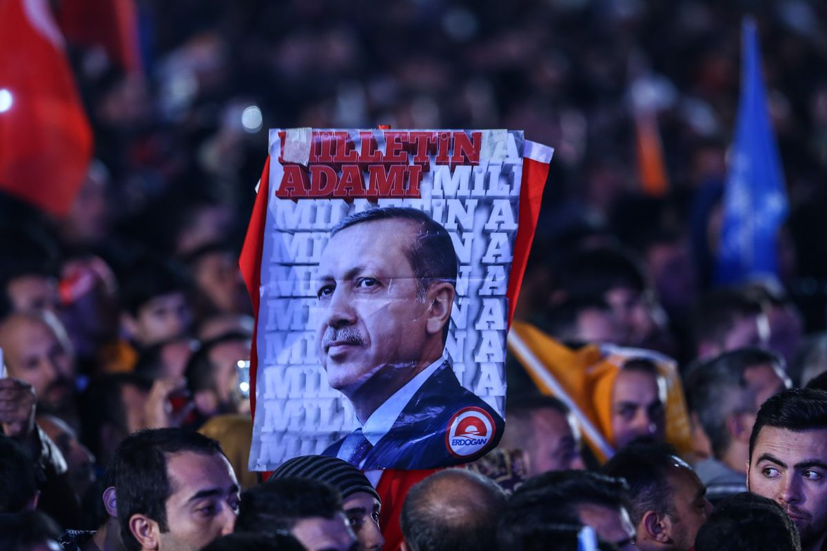 AKP supporters hold a placard with Erdoğan's face.