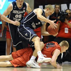 Brigham Young Cougars guard Tyler Haws (3) is fouled by Utah Utes center Jeremy Olsen (41) as Brigham Young Cougars forward Eric Mika (00) looks on during a game at the Jon M. Huntsman Center on Saturday, Dec. 14, 2013.