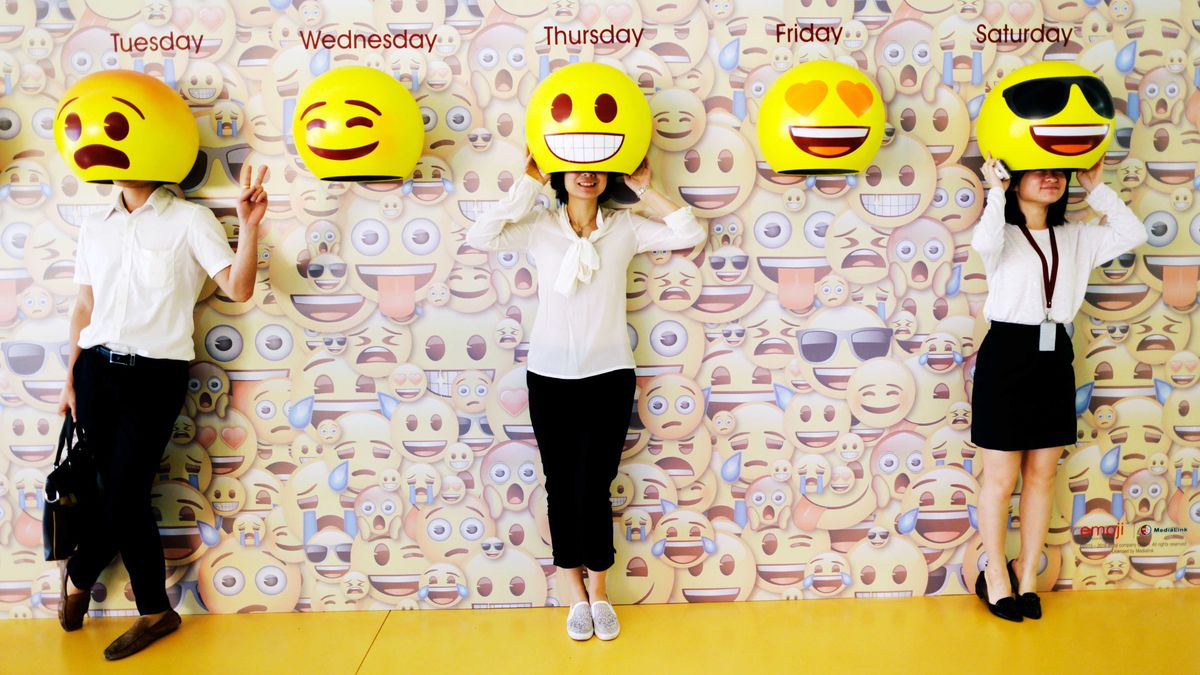 People pose for photos with emoji hats fixed on a wall in a shopping mall in China.