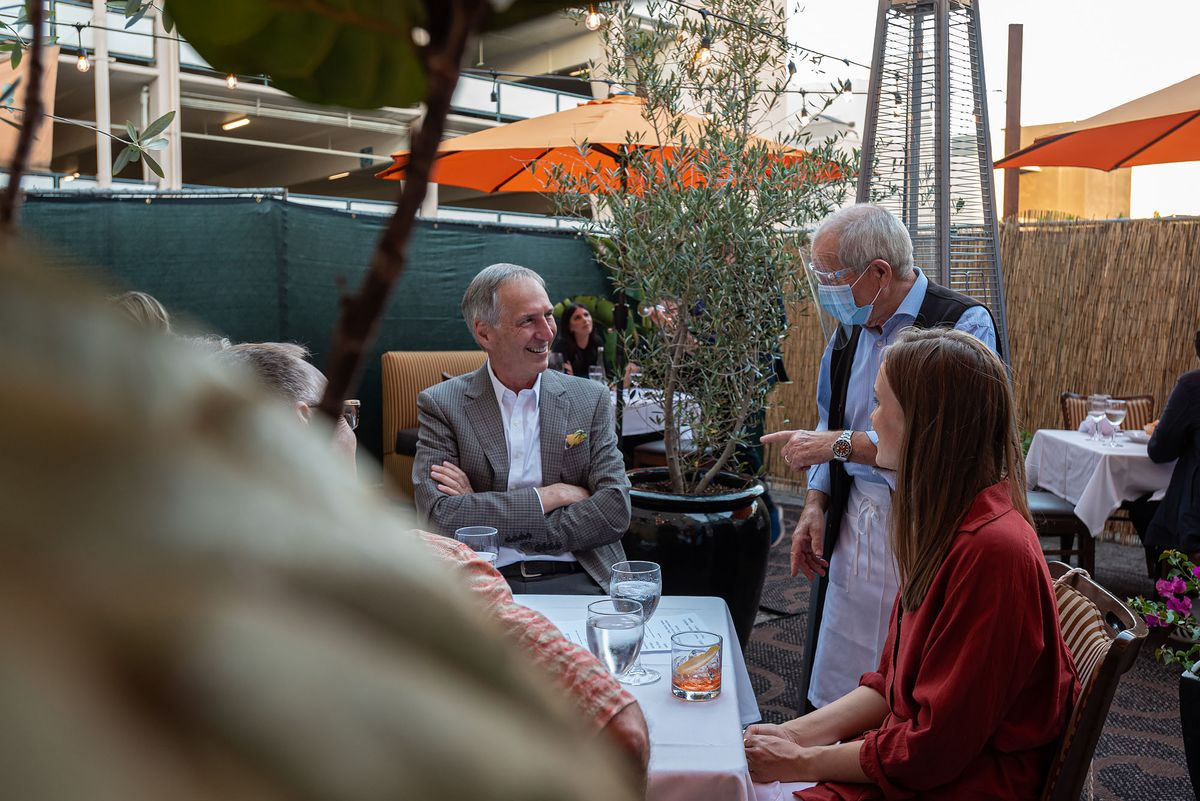 An aging restaurant owner behind a mask talks to customers.