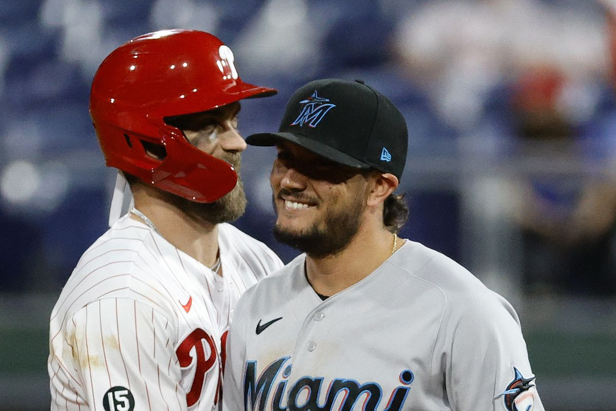 Bryce Harper of the Philadelphia Phillies and Miguel Rojas of the Miami Marlins share a laugh during the eighth inning at Citizens Bank Park