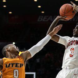 Arizona's Dylan Smith (3) shoots past UTEP's Nigel Hawkins (0) during the Arizona-University of Texas El Paso game in McKale Center on November 14 in Tucson, Ariz.