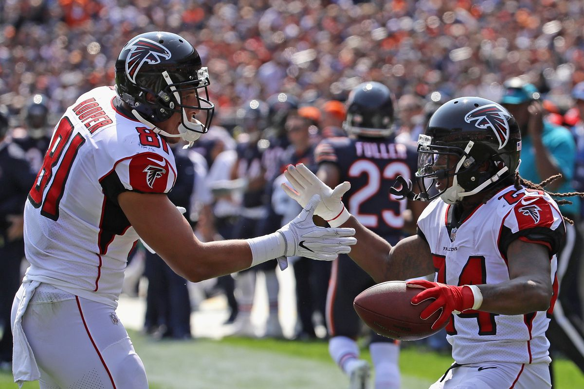 Devonta Freeman of the Atlanta Falcons is congratulated by Austin Hooper after running for a touchdown against the Chicago Bears during the season opening game at Soldier Field on September 10, 2017 in Chicago, Illinois.