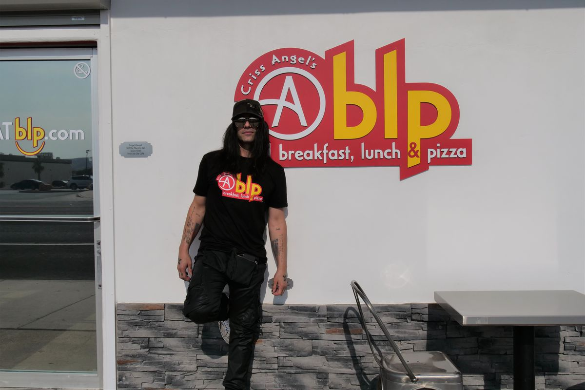 A man in a black hat, shirt, and pants with sunglasses on stands in front of a sign that says Cablp
