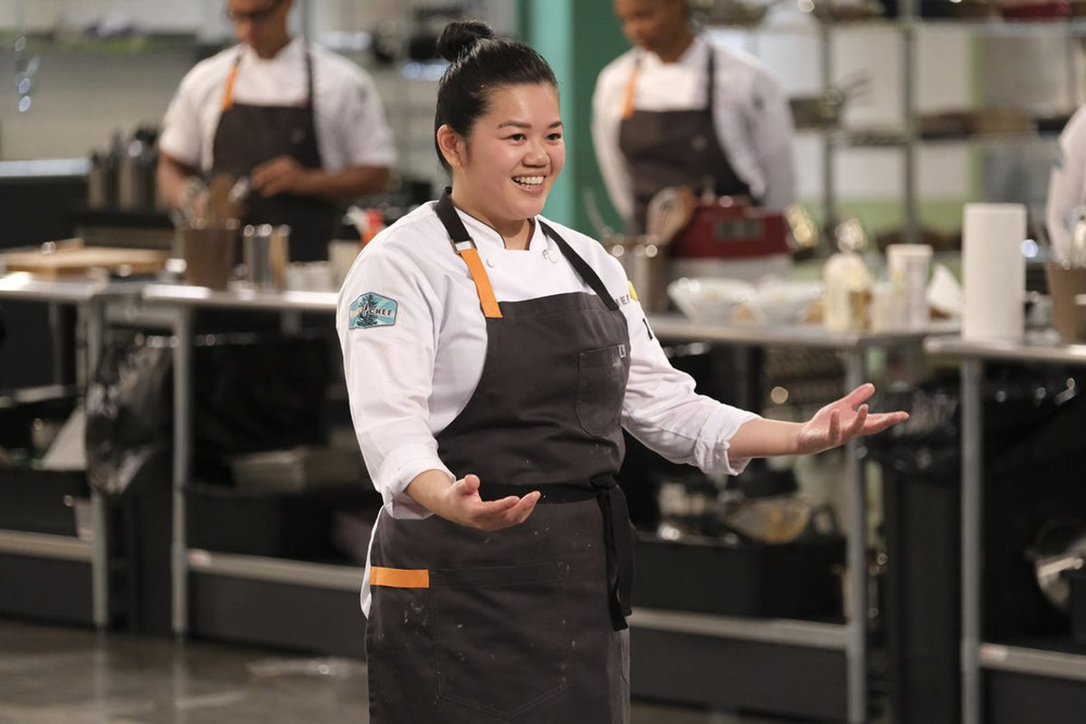 A chef in a white coat and gray apron holds out her hands