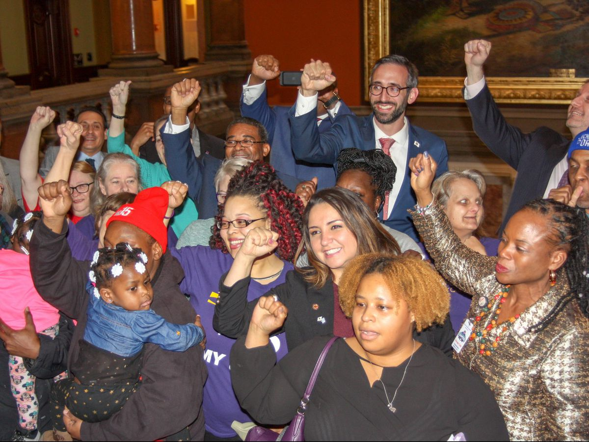 State Rep. Will Guzzardi joins activists on the Capitol rotunda after the bill to raise the state's minimum wage to $15 by 2025 passed the Illinois House on Thursday afternoon. The legislation, sponsored by Guzzardi, a Chicago Democrat, passed along parti