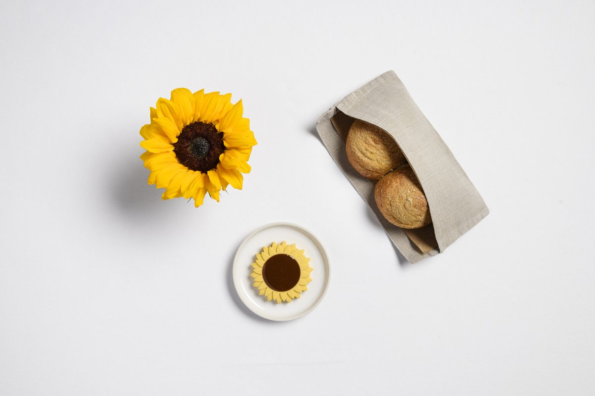 Sunflower butter, which takes the appearance of an Art Deco sunflower, sits on a white tablecloth next to rolls and an actual sunflower